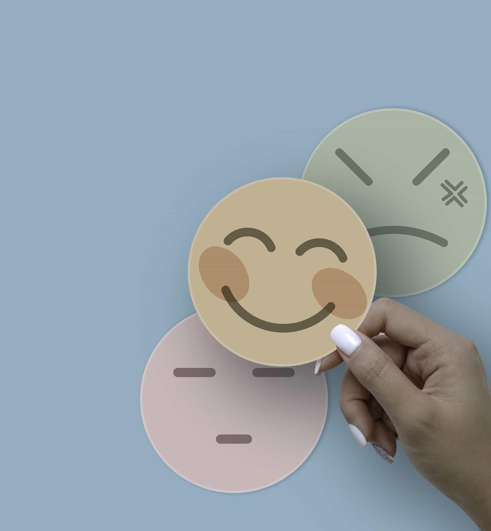 Una mano que sostiene un botón de cara triste, un botón de sonrisa y un botón de cara seria