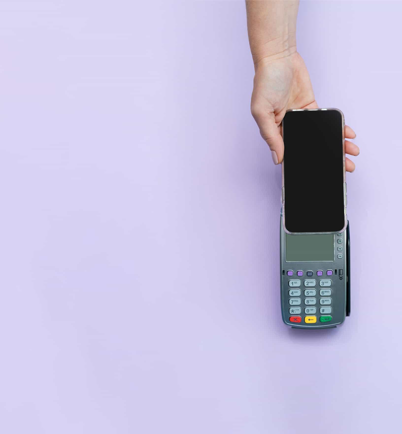 Una mano que sostiene un teléfono hacia arriba para usarlo como método de pago en un lector de tarjetas